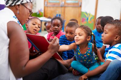 Image of African American daycare teacher reading to children