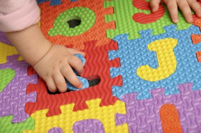 Image of child's hand playing with foam puzzle pieces.