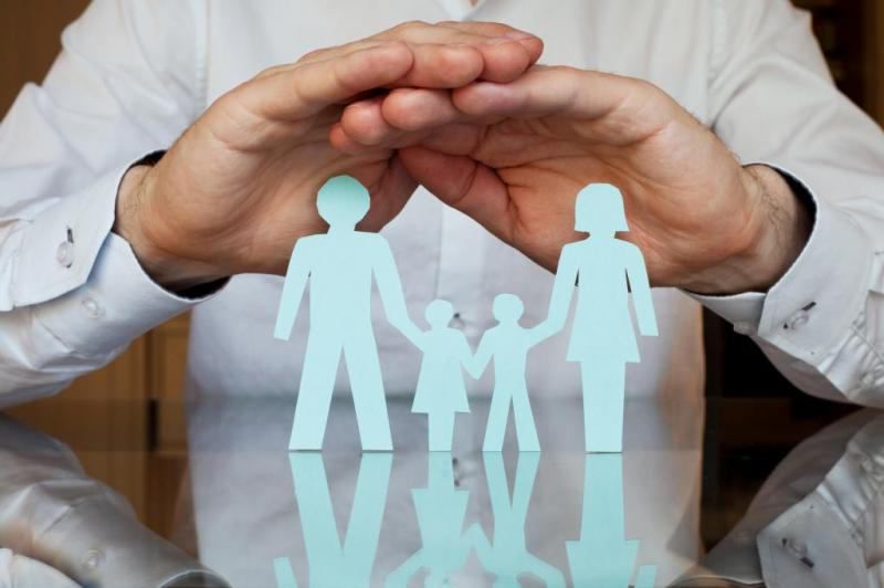 Image of hands covering paper cutout of family