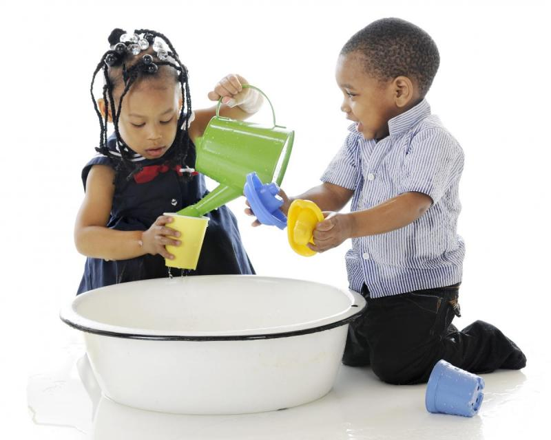 African-American children playing with watering can and plastic toys.