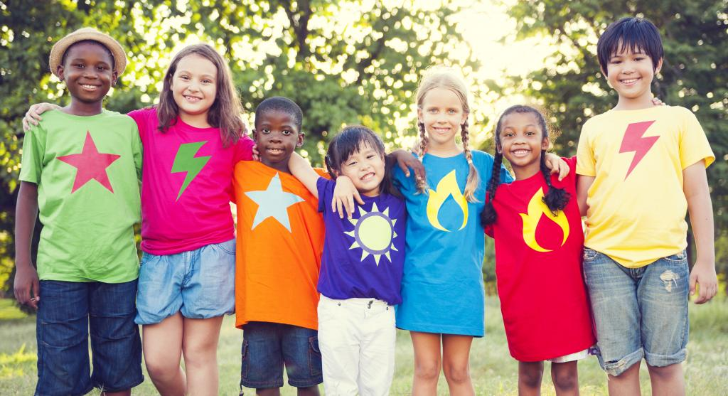 A diverse group of children, arms around each other with brightly-colored t-shirts