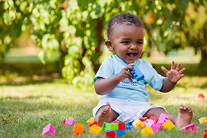 African American baby boy playing with blocks in the grass