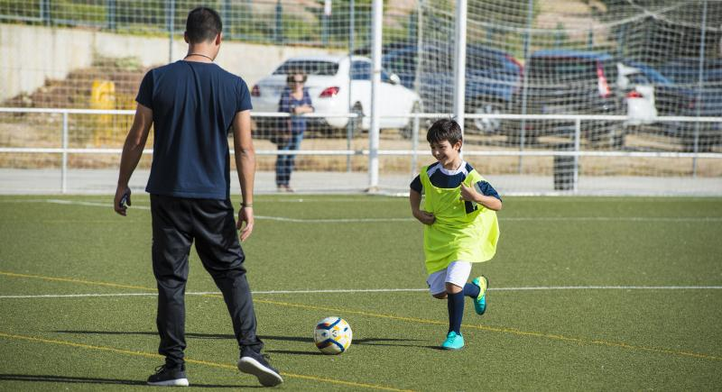 man coaching child in soccer